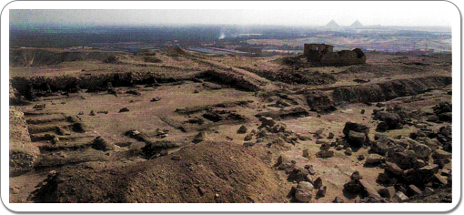 A view on the remains of the mortuary temple, with two of the pyramids of Giza in the background.